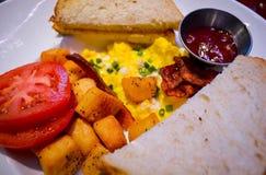 Fine su della prima colazione con pane tostato, le uova rimescolate ed il pomodoro Fotografia Stock