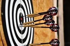 Fine su delle frecce dei dardi che sono attaccate nel bordo dell'obiettivo Fotografia Stock