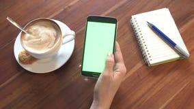 Fine su dello smartphone di uso della mano con lo schermo verde in caffè video d archivio