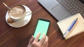 Fine su dello smartphone di uso della mano per lavoro in caffè stock footage