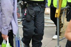 Fine su dello spruzzo delle manette di rappresentazione della cinghia di dovere della polizia e del gas del CS immagini stock libere da diritti