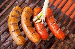 Fine su di grigliare le salsiccie sulla griglia del barbecue con una cipolla bianca lunga BBQ nel giardino Salsiccie bavaresi Fotografie Stock