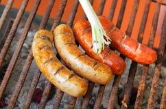 Fine su di grigliare le salsiccie sulla griglia del barbecue con una cipolla bianca lunga BBQ nel giardino Salsiccie bavaresi Immagine Stock