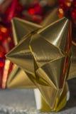 Fine su di un arco del regalo di natale dell'oro Fotografia Stock
