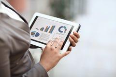Fine in su la donna di affari controlla il rapporto finanziario facendo uso della compressa digitale immagini stock