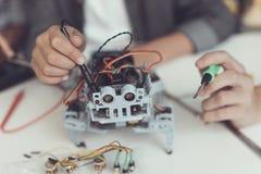 Fine in su La gente raccoglie un piccolo robot grigio Tengono gli strumenti differenti Fotografia Stock