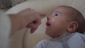 Fine in su La madre tocca il piccolo naso del ` s del figlio che trovandosi in sua greppia Sorriso affascinante del bambino illus archivi video