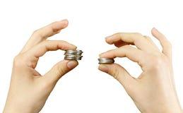 Fine in su Le mani confrontano due mucchi delle monete delle dimensioni differenti, i fotografie stock