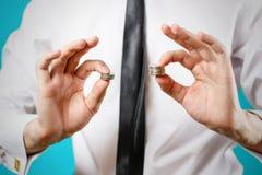 Fine in su Le mani dell'uomo d'affari confrontano due mucchi delle monete di differiscono Immagini Stock Libere da Diritti