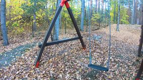 Fine su oscillazione in autunno, oscillazioni vuote abbandonate che ondeggiano nel vento all'aria aperta del campo da giuoco dei  archivi video