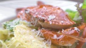 Fine su pasta italiana con il granchio rosso, l'erba fresca ed il formaggio sul piatto bianco Pasta tradizionale con frutti di ma archivi video