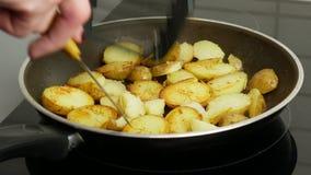 Fine in su Patate in una padella fritta in burro La mano di una donna fa girare i pezzi con un coltello Concetto dell'alimento video d archivio