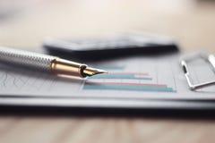 Fine in su penna con un PUNTO dell'oro sulla scrivania vaga del fondo Fotografia Stock Libera da Diritti