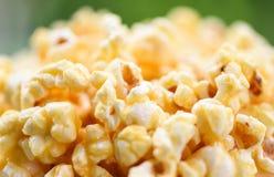 Fine su popcorn nel backgroubd di verde della natura e della tazza - sale dolce del popcorn del burro immagini stock