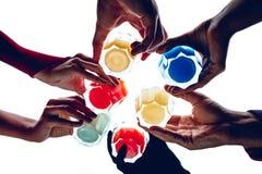 Fine in su Sei cocktail multicolori hanno tenuto in mani di sei genti su un fondo bianco Immagine Stock