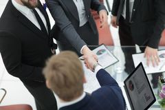 Fine in su stretta di mano dei partner commerciali al tavolo delle trattative fotografie stock libere da diritti
