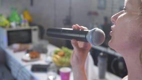 Fine in su una donna che grida ad un microfono una donna canta il karaoke in un microfono in una regolazione domestica 4k, movime video d archivio