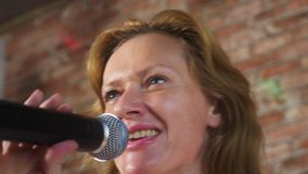 Fine in su una donna che grida ad un microfono una donna canta il karaoke in un microfono in una regolazione domestica 4k, movime stock footage