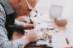 Fine in su Uomo anziano che ripara scheda madre dal PC fotografie stock libere da diritti