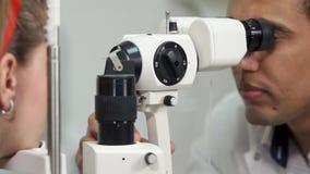 Fine sul colpo del fronte del ` s dell'uomo conduce biomicroscopy degli occhi in clinica archivi video