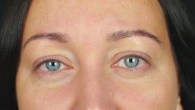 Fine sul fronte femminile con gli occhi aperti che sbattono le palpebre e che esaminano macchina fotografica archivi video