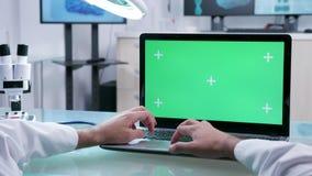 Fine sul metraggio di POV delle mani maschii del professionista che lavorano al computer portatile con lo schermo verde archivi video