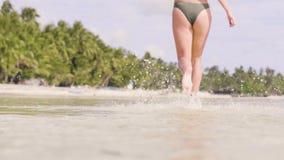 Fine sul piede femminile che corre sull'acqua di mare alla spiaggia tropicale Bella donna in bikini che corre sull'acqua alla riv stock footage