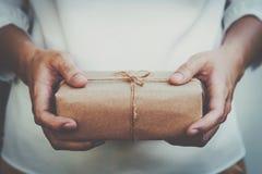 Fine sul presente e sulla tenuta della donna della mano dell'imballaggio del contenitore di regalo di Kraft fotografia stock libera da diritti
