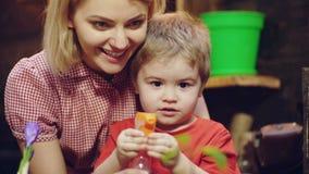 Fine sul ragazzo del bambino del ritratto con la madre facendo uso dello spruzzatore e della spruzzatura dei fiori ai vasi e del  stock footage