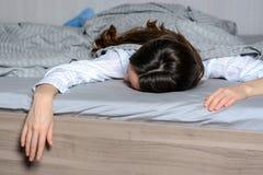 Fine sul ritratto di una donna vera stanca e che dorme in un letto domestico all'interno della posa come è caduto immagine stock libera da diritti