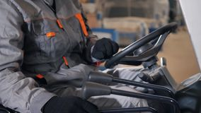 Fine - sul volante e sulle leve Equipaggi l'azionamento del carrello elevatore attraverso un magazzino in una fabbrica driver in  stock footage