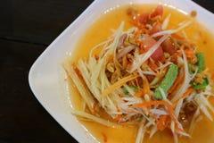 Fine sull'insalata piccante della papaia tailandese o tum del som in piatto bianco e nel fondo nero immagini stock libere da diritti