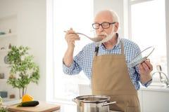 Fine sulla foto grigia dai capelli lui suo lui ospiti aspettanti di appetito del nonno che cucinano attesa di prova di gusto del  immagine stock
