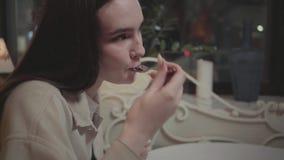 Fine sulla giovane donna che mangia piccolo pezzo di dolce saporito nel caffè La ragazza che gode del suo dessert nel moderno stock footage