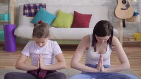 Fine sulla madre e sulla figlia che fanno yoga che si siede sul pavimento stock footage
