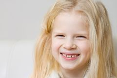 Fine sulla neonata bionda sorridente del fronte con i denti di latte ed i suoi denti in primo luogo molari Sanità, igiene dentale immagini stock libere da diritti