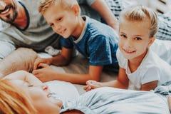 Fine sulla ragazza e sul ragazzo felici con i genitori a letto fotografia stock libera da diritti