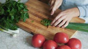 Fine sulle mani della donna con il coltello che taglia cipolla verde sul bordo di legno Alimento sano video d archivio