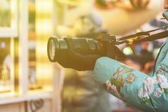 Fine sulle mani femminili che tengono un photocamera e sparare video nella via f fotografia stock