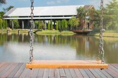 Fine sulle oscillazioni a catena vuote in campo da giuoco con il lago e sugli alberi verdi nei precedenti immagini stock libere da diritti