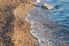 Fine sulle pietre della spiaggia sulla spiaggia Alba di estate sulla costa, isola di Corf?, Grecia Mare ionico della spiaggia wal immagini stock