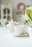 Fine tea cup and kettle on white table in kitchen Royalty Free Stock Photos