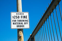 Fine for throwing material off bridge. Sign warning of fine if material is thrown from bridge Royalty Free Stock Photography