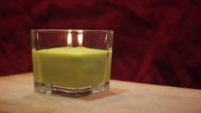 Fine verde della candela sulla rotazione 2 dell'interno con fondo rosso