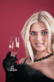 The fine woman. Portrait of the fine woman in an evening dress with a wine glass on a red background Royalty Free Stock Photography