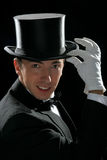 Fine young gentleman. Magician posing holding high hat with his hand Royalty Free Stock Photo