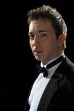 Fine young man. Portrait dressed in black suit on black background in studio Royalty Free Stock Photos