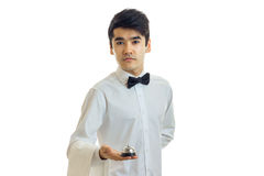 Fine young waiter with black hair in a shirt exactly stands and holds the Bell in the Palm of your hand Stock Photography