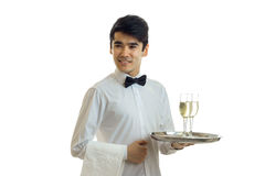 Fine young waiter looks straight smiles and holds a tray with glasses of champagne Royalty Free Stock Photo