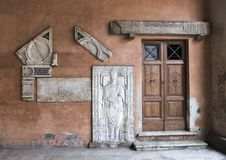 Finely carved tomb-slab of a 15th century bishop, set into the wall. Pictured is the right end of the narthex of San Lorenzo in Lucina. It houses a finely carved royalty free stock image